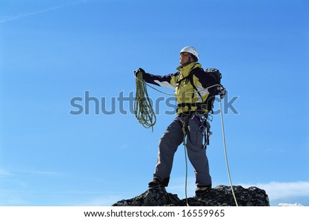 Mountaineer on top of mountain summit - stock photo