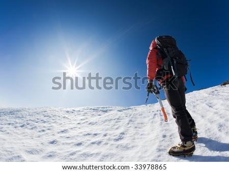 Mountaineer reaching the top of a snowcapped mountain peak. Horizontal frame. - stock photo