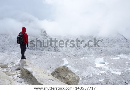 Mountaineer standing near Khumbu Icefall - one of the most dangerous stages of the South Col route to Everest's summit,Nepal - stock photo
