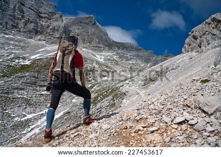 Mountaineer standing on a slope on a path to Kukova Spica mountain looking up hill, Slovenia - stock photo