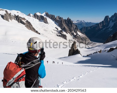 Mountaineer taking picture with a camera in the mountains. Mont Blanc Glacier, Chamonix, France, Europe. - stock photo