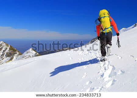 Mountaineer walking on a snow covered trail in sunny winter day - stock photo