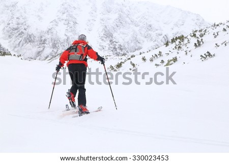 Mountaineer woman ascending on touring skis under snowfall  - stock photo