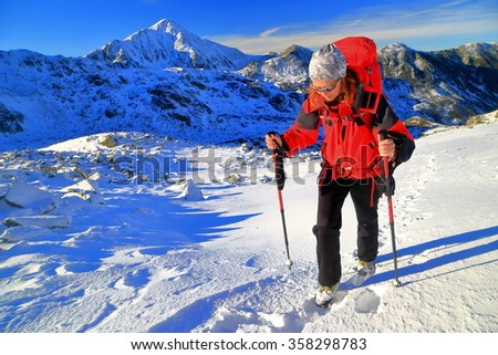 Mountaineer woman carries a backpack on snowy mountain trail - stock photo