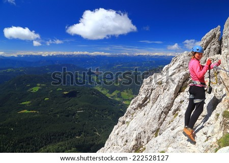 "Mountaineer woman climbs on via ferrata ""Passo Santner"", Catinaccio massif, Dolomite Alps, Italy - stock photo"