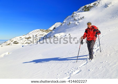 Mountaineer woman in sunny winter day in Retezat mountains, Romania - stock photo