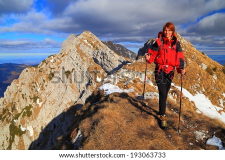 Mountaineer woman on grass covered ridge - stock photo