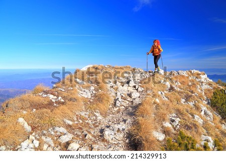 Mountaineer woman on top of grass covered summit in sunny day - stock photo