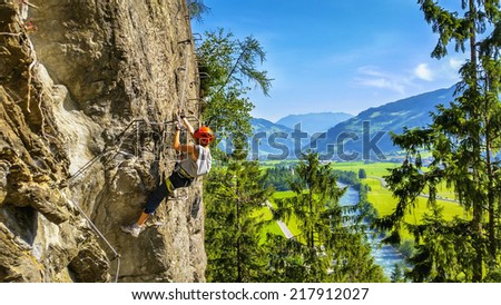 Mountaineer woman traverses on via ferrata, Zillertal Alps, Austria - stock photo