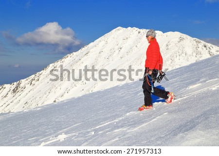 Mountaineer woman using crampons and ice axe on snow covered mountain slope - stock photo