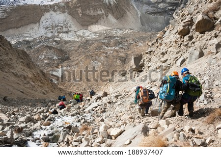 Mountaineering group descending from Tharpu Chuli high camp, Annapurna region, Nepal - stock photo