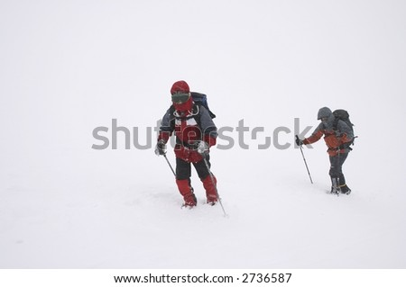 mountaineers on bad winter weather (snow grain visible) - stock photo