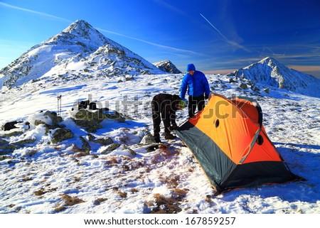 Mountaineers preparing camp site on snowy mountain - stock photo