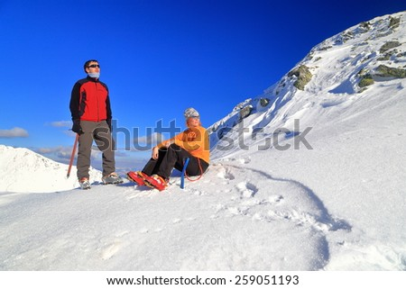 Mountaineers resting on snow covered mountain in winter - stock photo