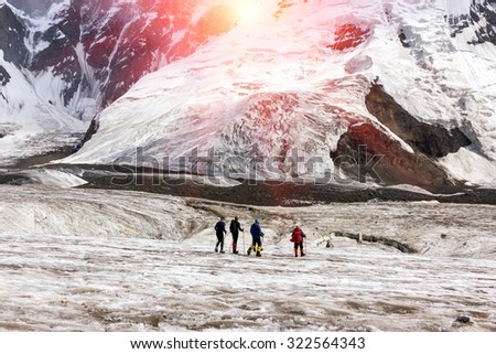 Mountaineers Walking Across Large Glacier Group of Mountain Climbers with High Altitude Boots and Clothing Crossing Ice Section During Ascent of Alpine Expedition in Asia Mountain Area Sun Shining - stock photo