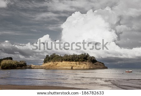 Mountainous clouds rise above a sandstone peninsula at Sidari on the north coast of Corfu, Greece, with a fashionable desaturation applied - stock photo