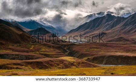Mountainous valley scene in Denali National Park during Autumn with dramatic lighting over glacial valley stream with braided channel. - stock photo