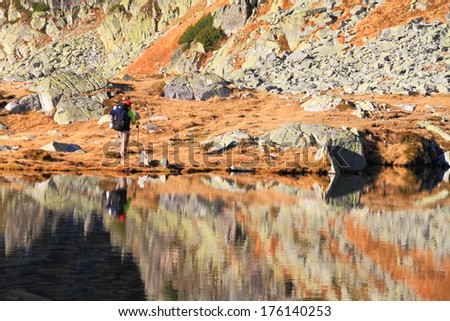 Mountains and backpackers reflected by calm waters of glacier lake - stock photo