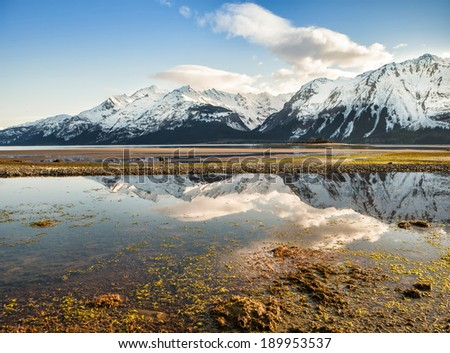 Mountains and clouds reflected in the outgoing tide of the Chilkat Inlet near Haines Alaska in spring. - stock photo