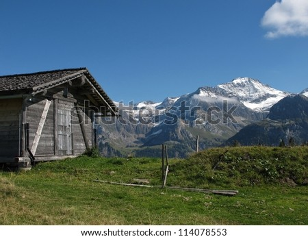 Mountains And Old Shed With Timber Roof - stock photo