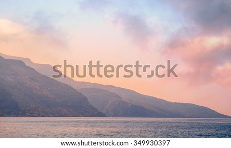 Mountains landscape at sunrise - cloudy sky in pastel colors for your design, serenity and rose quartz. Romantic mountain landscape - seaside view and blue hills silhouettes in a fog. - stock photo