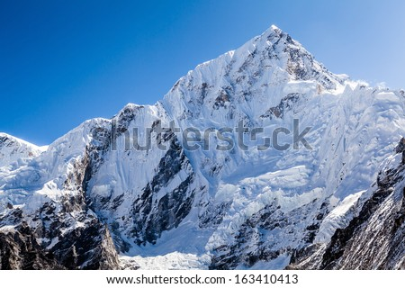 Mountains landscape in Everest National Park. White snow and avalanche on Nuptse mountain 7864m over Khumbu glacier in Himalayas, Nepal - stock photo