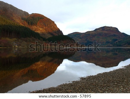 Mountains reflect in a Scottish Loch - stock photo