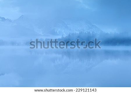 mountains reflected in lake in dense dusk fog, Germany - stock photo