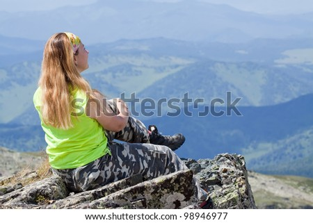 mountains tourist on mountain peak and looking to  valley below - stock photo