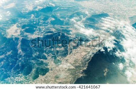 mountains view through airplane window at high altitude - stock photo