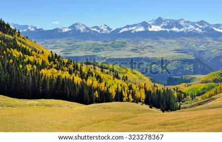 mountains with colorful yellow, green and red aspen during foliage season on Last Dollar road in Colorado - stock photo