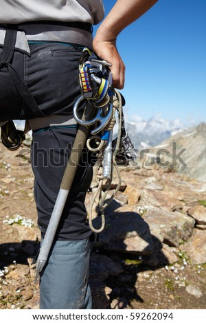 Mountaneer with climbing equipment in the mountains - stock photo