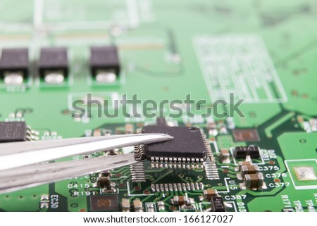 Mounting microchip on electronic circuit board with tweezers - stock photo