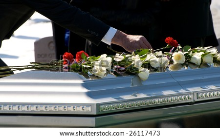 Mourner placing flower on casket at Arlington National Cemetery - stock photo