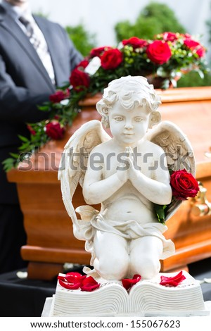 Mourning man on funeral with red rose standing at casket or coffin - stock photo