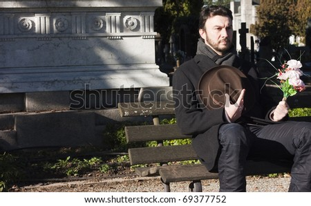 Mourning Man Seating on a Bench in a Graveyard - stock photo
