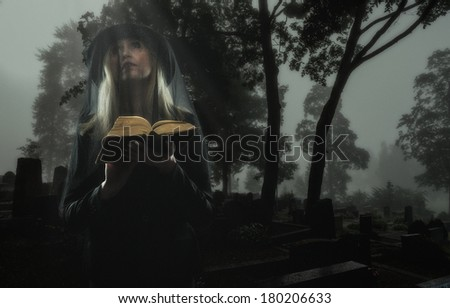 Mourning widow praying on a grave at the cemetery - stock photo