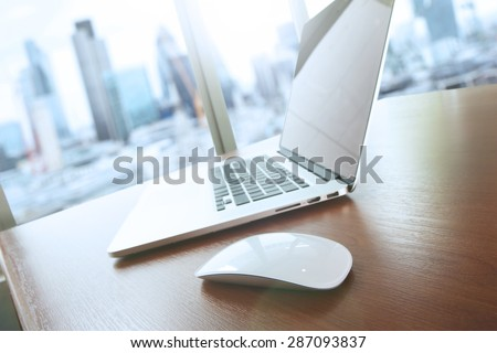 mouse and laptop computer is on wooden desk as workplace concept with overcast effect - stock photo