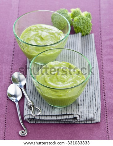 Mousse Cream of broccoli soup in glass bowls on a purple tablecloth - stock photo