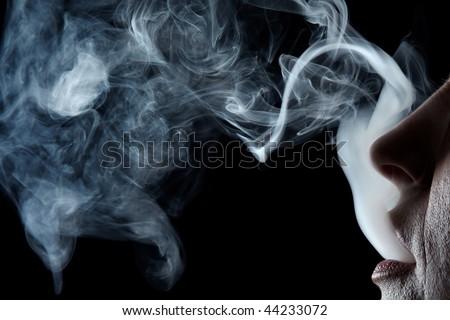 Mouth exhaling cigarette smoke on black background - stock photo