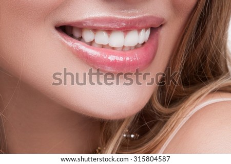 Mouth open.A beautiful smile woman close-up,straight white teeth,light makeup.mouth open.woman is smiling while being at the dentist.Closeup of smile with white healthy teeth.Dental health background. - stock photo