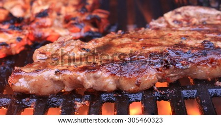 Mouth watering steak and chicken thighs being grilled on cast iron grates over charcoal - stock photo