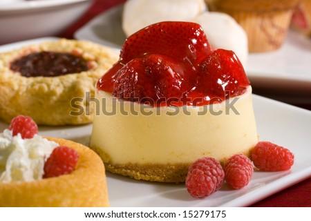 Mouthwatering cheesecake with strawberries on top, raspberry thumbprint scone, raspberry shortcake and fresh raspberries make up this shot. - stock photo
