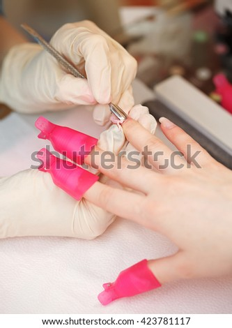 Move aside the cuticle close-up in a beauty salon. Manicure process. - stock photo