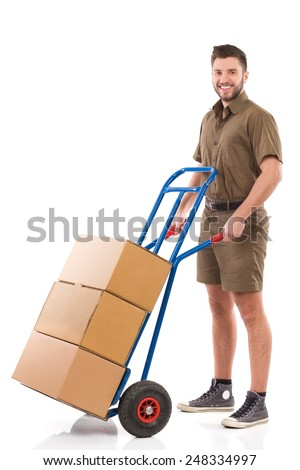 Mover posing with a delivering cart. Happy delivery man standing with a push cart. Full length studio shot isolated on white. - stock photo