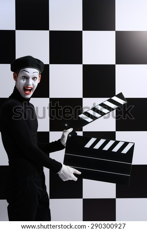 Movie actor and a mime posing with clapper board with different emotions. Chess board background. Cinema industry.  - stock photo