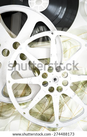 Movie cinema reels on 35 mm unrolled film vertical on neutral background - stock photo
