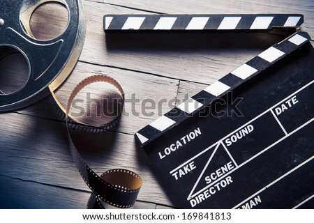 Movie clapper and film reel on a wooden background - stock photo