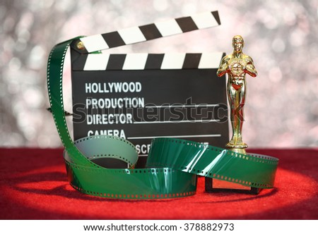 Movie clapper board and film roll in front glittering  background - stock photo