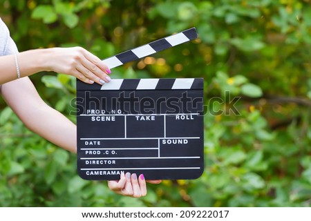 Movie clapper board in hands against green background - stock photo